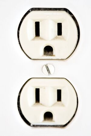 Old-Fashioned, ceramic electrical outlet on a white wall. Stock Photo