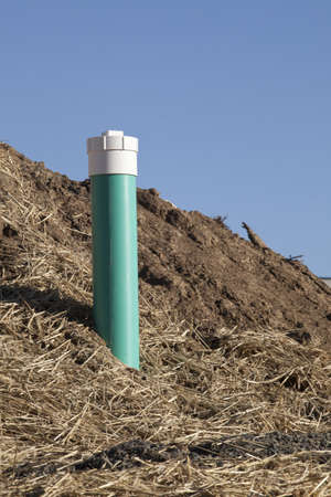venting: Green plastic sewer pipe for venting gas at a construction site