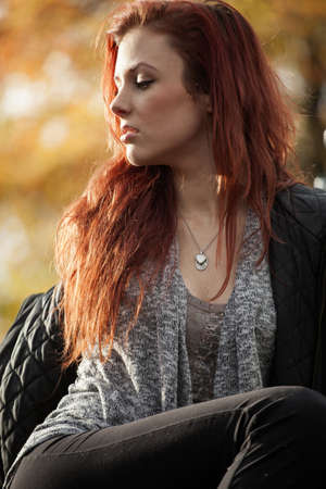 auburn hair: Young woman looking away and a beautiful orange background.