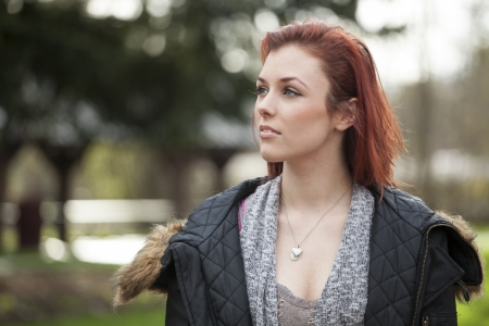 auburn hair: Young woman with green eyes staring off into the distance.