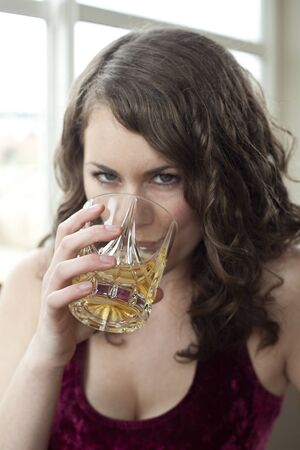 scotch whisky: Young woman drinking a glass of Scotch. Stock Photo