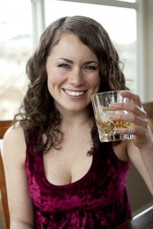 table top: Young woman drinking a glass of Scotch. Stock Photo
