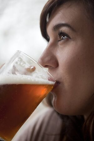 tightly: Young woman drinking a pint of beer at a pub