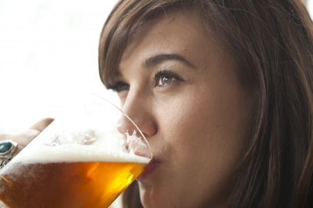 ipa: Young woman drinking a pint of beer at a pub