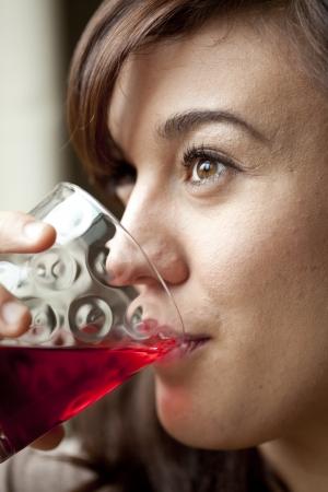 Jeune femme buvant un verre de jus de canneberge.