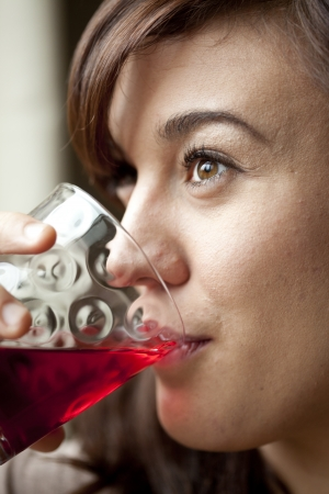 arandanos rojos: Mujer joven que bebe un vaso de jugo de ar�ndano. Foto de archivo