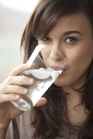 Beautiful young woman drinking water in the morning. photo