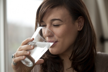 Beautiful young woman drinking water in the morning.