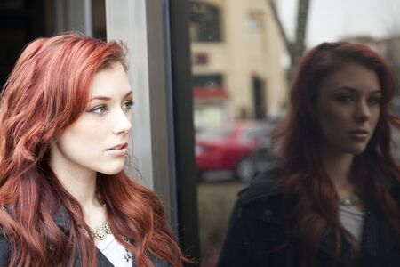 reflected: Beautiful young woman with red hair reflected in a shop window. Stock Photo
