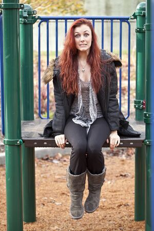 auburn: Young woman with beautiful red hair on playground equipment with a surprised look on her face.