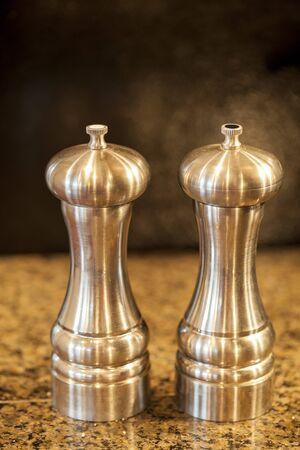 pepper grinder: Salt and pepper shakers on a granite counter top.