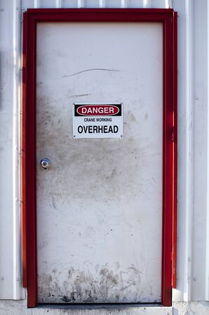 scuffed: Very dirty white door with danger sign on it