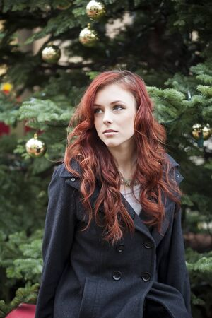 Young woman with beautiful red hair in front of a Christmas tree. photo