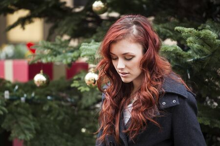 auburn: Young woman with beautiful red hair in front of a Christmas tree.