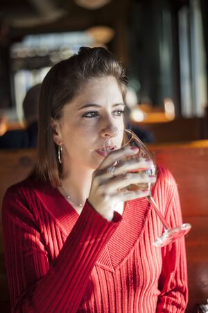 auburn hair: Portrait of a young woman with a glass of white wine