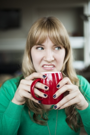 Portrait of a young woman staring straight making an ugly face while holding a cup of coffee.