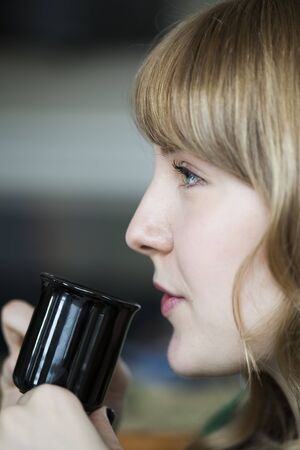 Portrait of a young woman staring straight ahead into the camera holding a cup of coffee. photo