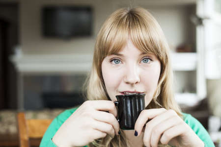 Pretty young blonde woman drinking her morning coffee. photo