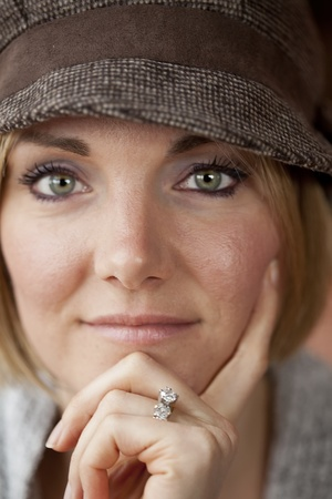 30 something women: Young woman in cute brown hat staring straight ahead into the camera