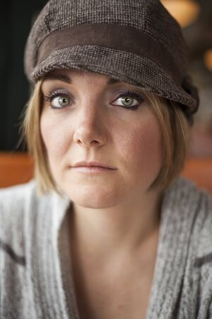 30 something: Young woman in cute brown hat staring straight ahead into the camera