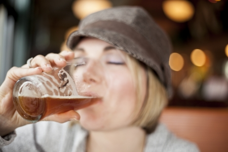 Young woman in cute brown hat drinking a beer. Stock Photo