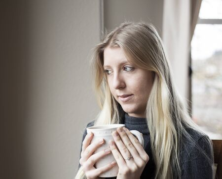 Pretty young blonde woman drinking her morning coffee. Stock Photo - 17471166