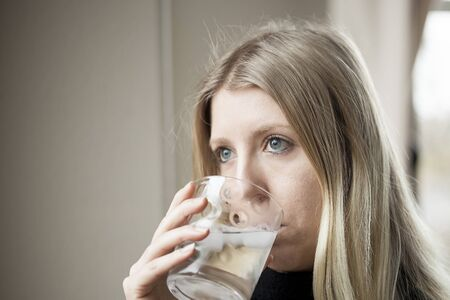 Pretty young blonde woman drinking a glass of water. photo