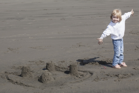 Cute blonde child playing at the beach next to a sand castle  photo