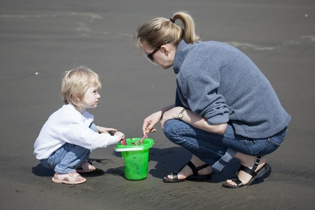 Cute blonde child and her mother playing at the beach with green bucket and pink shovel. photo