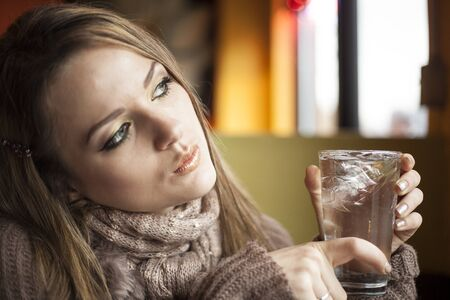 Portrait of a young woman with beautiful blue eyes drinking a glass of ice water. photo