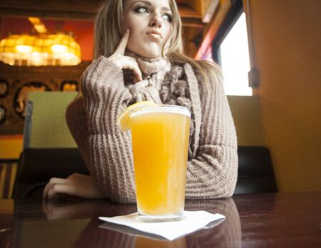 Portrait of a young woman with beautiful blue eyes drinking a pnt of hefeweizen beer. photo