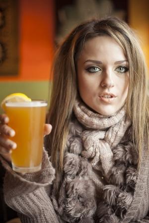 pelo castaño claro: Retrato de una mujer joven con los ojos azules hermosos que beben una cerveza pnt de hefeweizen. Foto de archivo