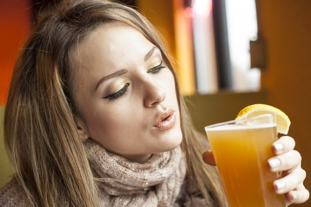 Portrait of a young woman with beautiful blue eyes drinking a pint of hefeweizen beer. photo
