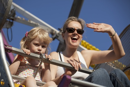 amusement park ride: Beautiful, blonde-haired mother and daughter on a ride at the fair.