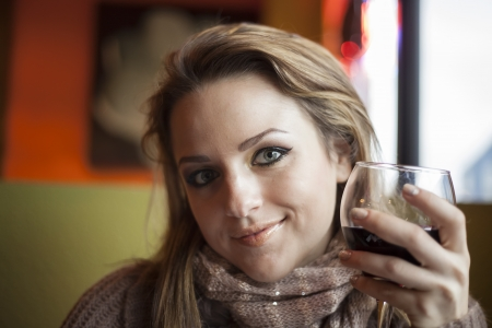 syrah: Portrait of a young woman with beautiful blue eyes drinking a glass of red wine.