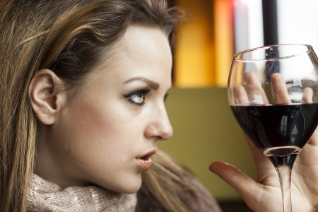Portrait of a young woman with beautiful blue eyes drinking a glass of red wine. photo