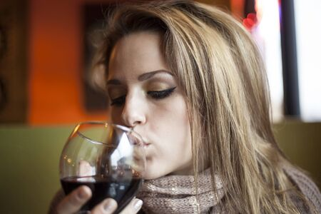 Portrait of a young woman with closed eyes drinking a glass of red wine. photo