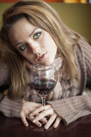 pelo castaño claro: Retrato de una mujer joven con los ojos azules hermosos que beben una copa de vino tinto. Foto de archivo