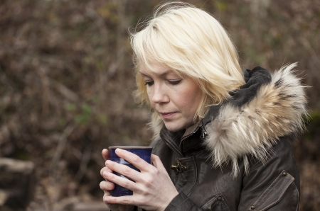 Portrait of a blonde woman holding a cup of coffee.