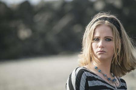 blonde yeux bleus: Portrait d'une jeune femme à la plage.