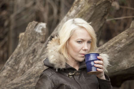 warm clothing: Portrait of a blonde woman holding a cup of coffee.