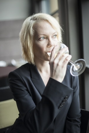 causcasian: Portrait of a blonde woman drinking a glass of white wine.
