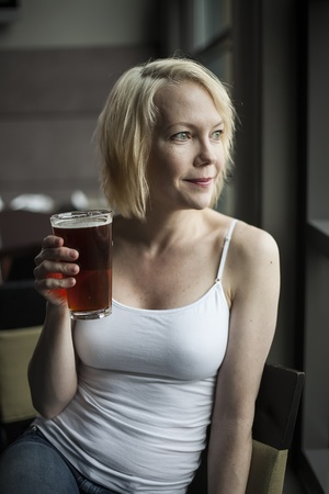 Portrait of a blonde woman drinking a glass of pale ale.