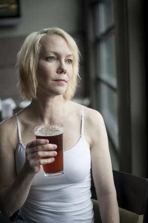 causcasian: Portrait of a blonde woman drinking a glass of pale ale.
