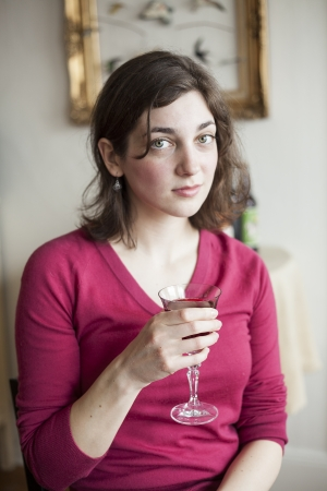 Portrait of a beautiful young woman drinking a glass of red wine  photo