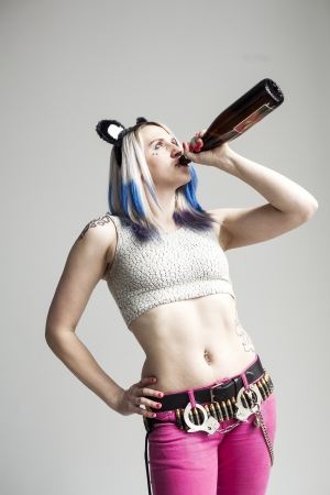 Portrait of a beautiful young woman with blue hair drinking a bottle of wine Stock Photo - 18426890