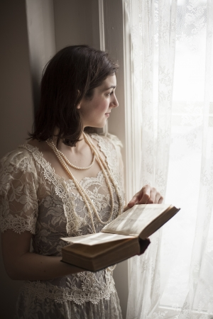 Portrait of a young woman in a vintage white wedding dress reading a book  Stock Photo - 18448297