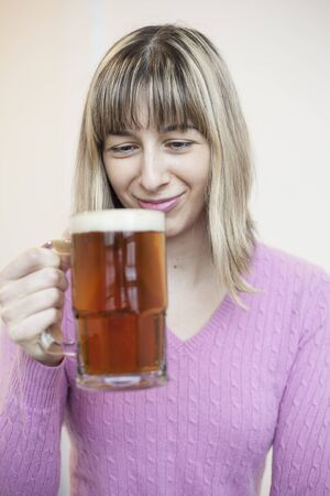 anticipating: Beautiful young woman drinking a mug of beer  Stock Photo