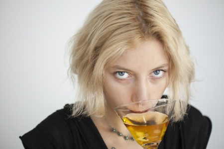 Portrait of a blonde woman with blue eyes drinking a martini.
