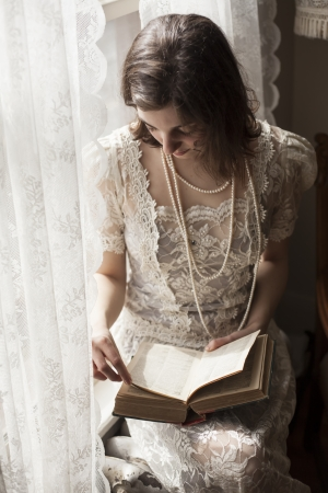 window curtains: Portrait of a young woman in a vintage white wedding dress reading a book. Stock Photo